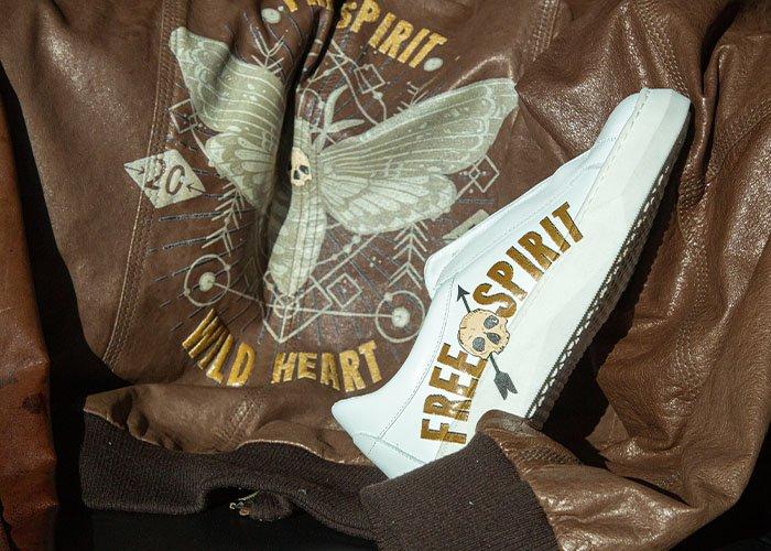 MondoAgile - Stampa Diretta - Dettagli stampa scritta free spirit su sneaker bianca e giacchetto in pelle da motociclista